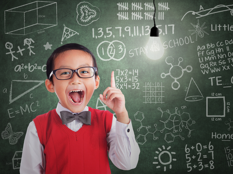 A schoolboy wearing glasses by a blackboard in a classroom