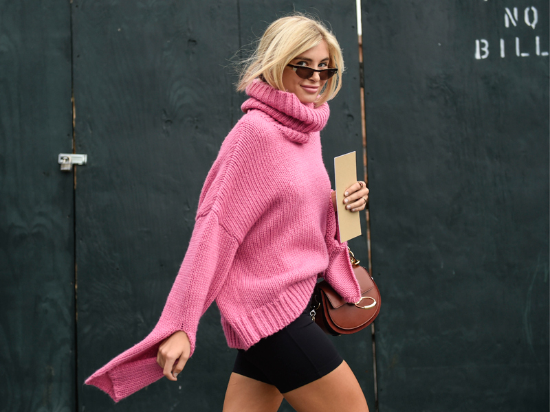 Blonde woman wearing a bright pink knit jumper and black shorts