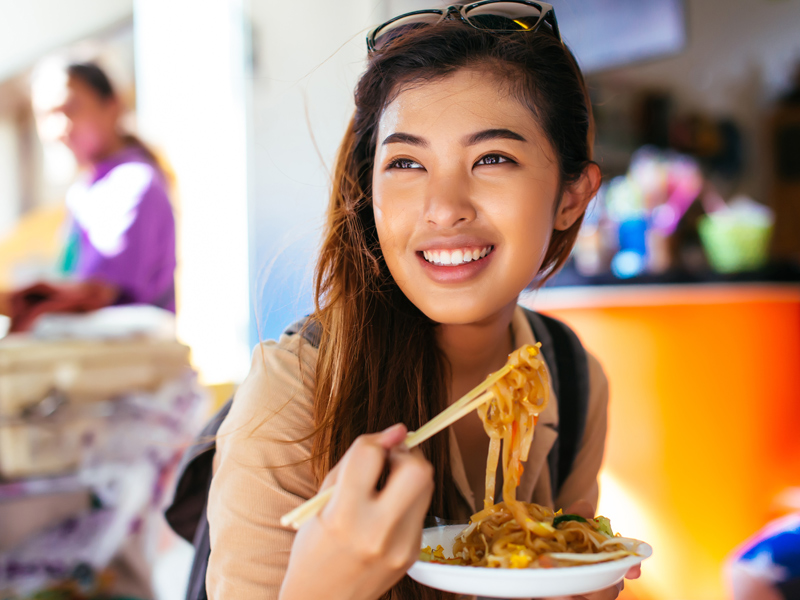 Young woman eating noodle dish with chopsticks