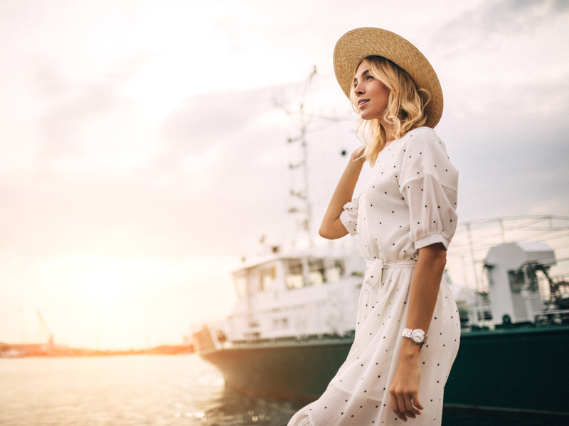 Young woman wearing polka-dot dress and straw hat standing by a boat
