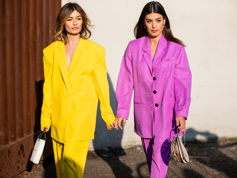Two women wearing brightly coloured loose suits at Fashion Week